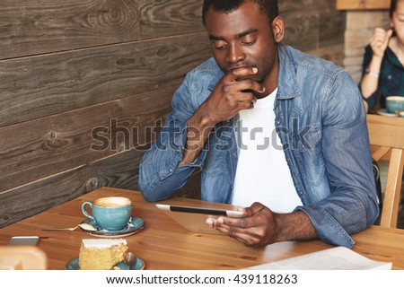 Handsome dark-skinned man looking pensively at his tablet and covering up mouth with fingers. African guy in blue denim is so busy with reading messages or articles that he hasn't finished his coffee. - stock photo