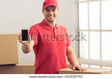 Handsome delivery worker is showing a smartphone, looking at camera and smiling while standing among cardboard boxes. Phone in focus - stock photo