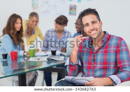 Handsome designer sit in his office with colleagues discussing behind - stock photo