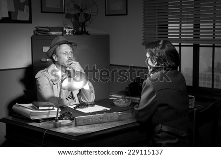 Handsome detective at office desk interviewing a young woman, 1950s film noir style. - stock photo