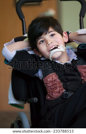 Handsome disabled eight year old biracial boy smiling and relaxing in wheelchair - stock photo