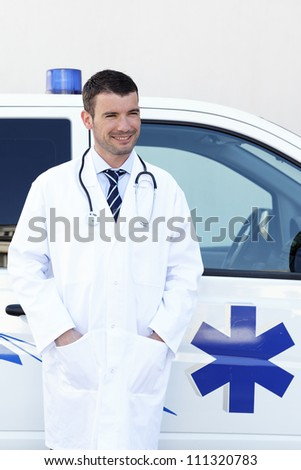 handsome doctor waiting in front of ambulance - stock photo