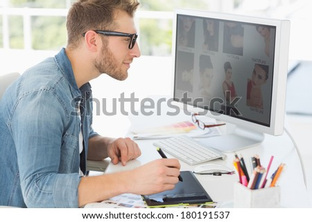 Handsome editor working with digitizer in creative office - stock photo