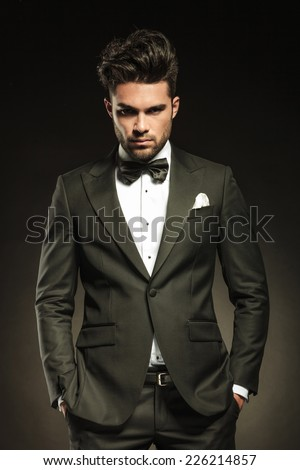 Handsome elegant business man looking at the camera while holding both hands in pockets. On black studio background. - stock photo