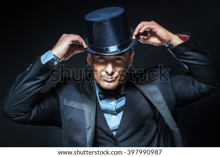 Handsome elegant man posing in suit and hat. Black background. - stock photo