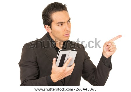 handsome elegant young latin man wearing a suit posing using tablet pointing to the side isolated on white - stock photo
