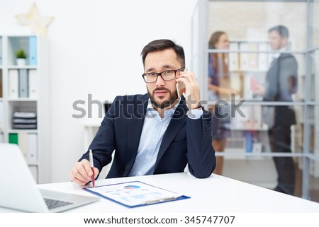 Handsome employer calling at workplace in office - stock photo