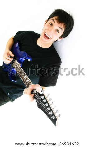 handsome excited young man lies on the floor and plays guitar - stock photo