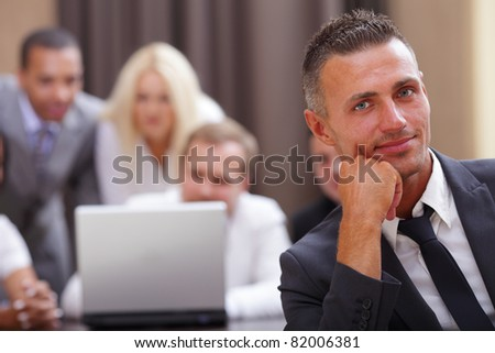 Handsome executive businessman with his team working behind - stock photo