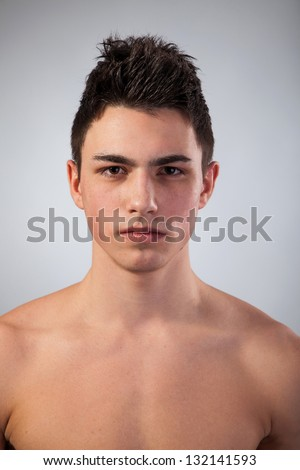 Handsome face of a young man. Isolated on grey background. - stock photo