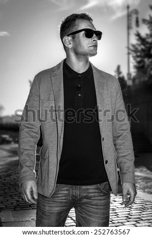 handsome fashion man in casual clothes and sunglasses walking in city - stock photo