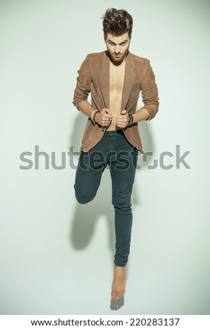 Handsome fashion man jumping and pulling his jacket while looking at the camera, on grey background - stock photo
