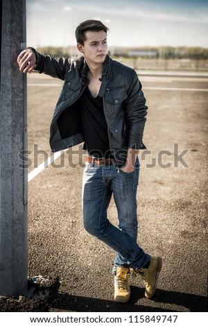handsome fashion man on the standning on the car parking street - stock photo