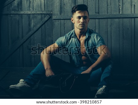 Handsome fashionable sexy sensual muscular young macho man with bare torso and stylish hair in jeans shirt holding sport bag indoor sitting on wooden background, horizontal picture - stock photo