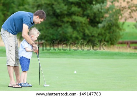 handsome father and his cute son playing golf together - stock photo