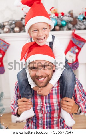 Handsome father and his son are celebrating New Year. The parent is holding his son on his shoulders. The boy is embracing his father with joy. They are smiling in red hat - stock photo