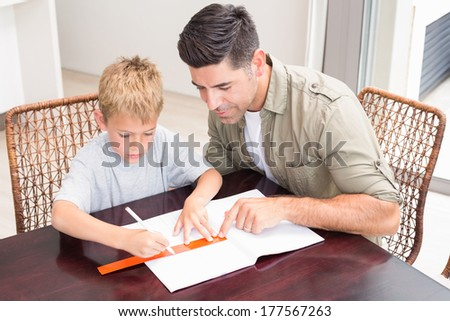 Handsome father helping son with homework at table at home in kitchen - stock photo
