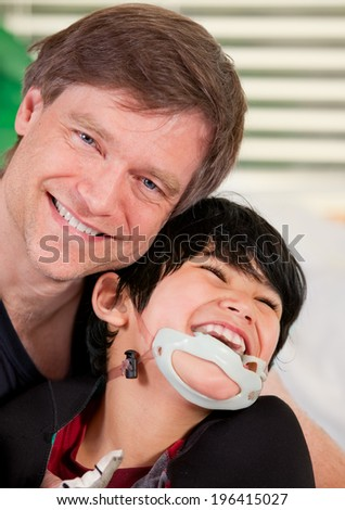 Handsome father holding disabled seven year old son, smiling together - stock photo