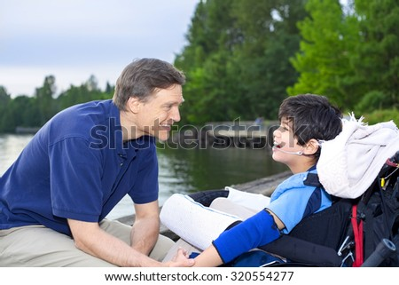 Handsome father in forties talking to disabled nine year old son in wheelchair by a lake - stock photo