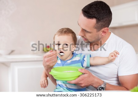 Handsome father is feeding his son with concentration. He is sitting in the kitchen and holding the boy on his knees. The toddler is eating porridge with appetite. Copy space in left side - stock photo