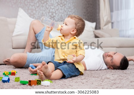 Handsome father is lying on flooring near his sun. He is looking at kid with love and gently smiling. The boy is sitting and drinking water from a bottle with concentration - stock photo