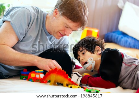 Handsome father playing cars with disabled son on floor mat - stock photo