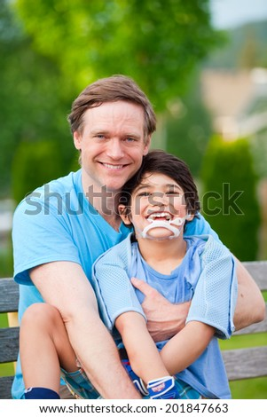 Handsome father sitting with smiling disabled seven year old son outdoors - stock photo