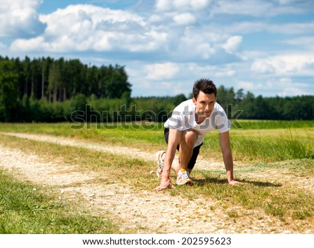 Handsome fit male runner in the ready position to sprint crouching down on a rural track in scenic countryside as he prepares to do his daily exercise and training session - stock photo
