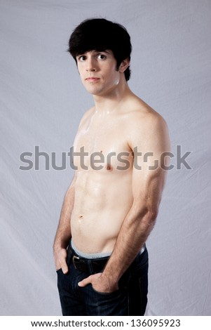 Handsome fit male standing with his shirt off and his hands in his pockets, his muscles on his arm well defined. Looking at the camera with a serious, focused expression - stock photo