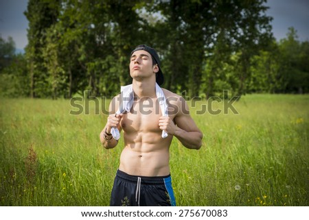 Handsome fit young man at countryside, in front of field or grassland, shirtless wearing cap, resting and relaxing after sport - stock photo