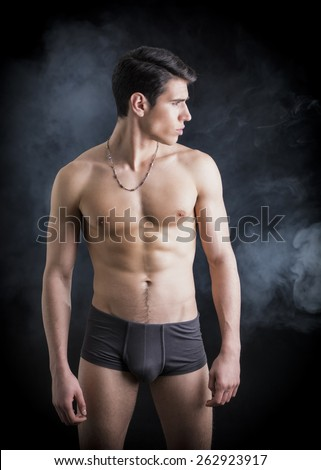 Handsome, fit young man wearing only underwear standing on black background, looking away - stock photo