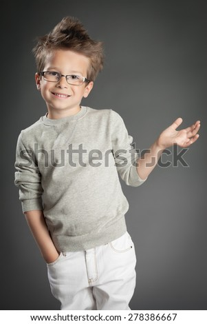 Handsome five year old boy posing in studio over gray background. Boy wearing reading glasses.  - stock photo