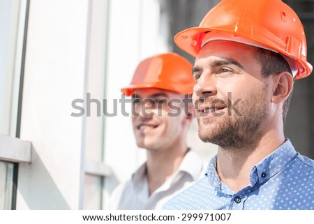 Handsome foreman and architect are standing and looking through the window dreamingly. They are smiling with hope. Their project was approved - stock photo