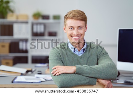 Handsome friendly young businessman sitting leaning on a table in the office looking at the camera with a beaming smile - stock photo