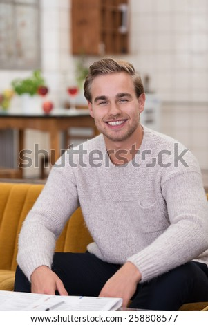 Handsome friendly young man sitting on a sofa relaxing and smiling at the camera - stock photo