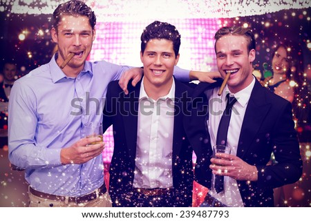 Handsome friends having a drink together against gold and red lights - stock photo