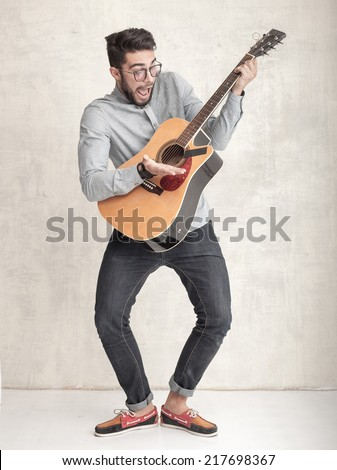 handsome funny man playing an acoustic guitar against grunge wall - stock photo