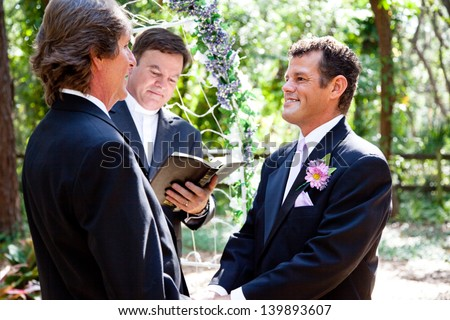 Handsome gay couple getting married in beautiful outdoor ceremony. - stock photo