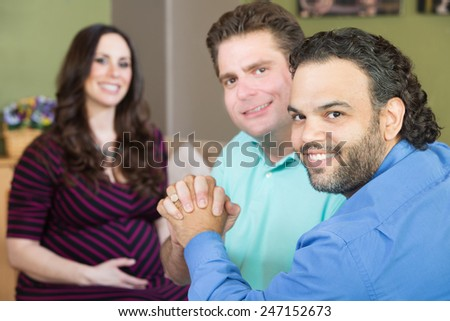 Handsome gay men holding hands with smiling surrogate mother - stock photo
