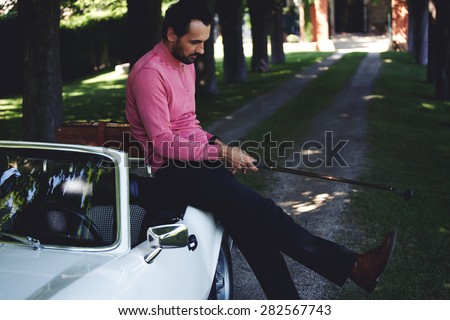 Handsome golf player holding a driver or golf club while getting ready for a day on the course, wealthy man leaning on his convertible luxury car preparing for golf game at recreation time on weekend  - stock photo