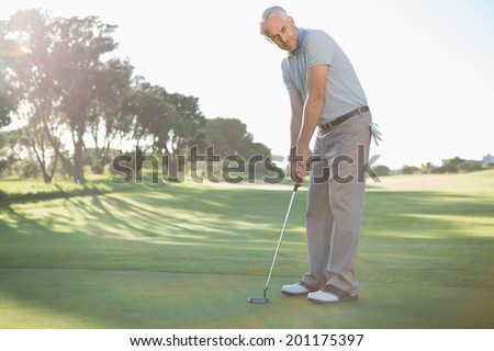 Handsome golfer putting ball on the green on a sunny day at the golf course - stock photo