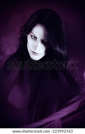 Handsome gothic man over dark background. - stock photo
