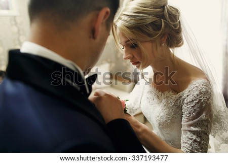 Handsome groom and beautiful blonde bride exchanging wedding rings - stock photo