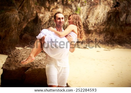 handsome groom carry beautiful bride on his arms at sand beach against rocks and cliffs - stock photo