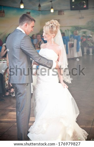 Handsome groom hugging bride during their first dance - stock photo