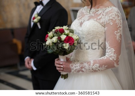 Handsome groom in black suit and stylish bride holding wedding bouquet closeup - stock photo