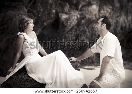 handsome groom looks at beautiful bride sitting on the rock at the sand beach - stock photo