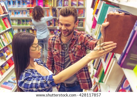 Handsome guy and beautiful girl are looking at each other and smiling while holding the same book in the bookshop, another girl in the background - stock photo