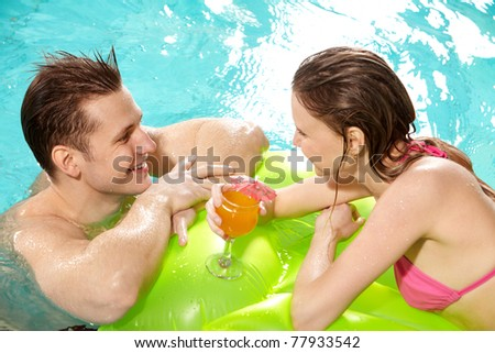 Handsome guy and pretty girl looking at one another in swimming pool - stock photo
