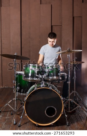 Handsome guy behind the drum kit on a brown background - stock photo
